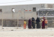 In this Thursday, Oct. 1, 2015 photo, Syrian refugees stand by a fence to see their family members getting on a return bus for women and children to the Syrian border, at the U.N.-run Zaatari refugee camp near Mafraq, northern Jordan. The trailer truck behind the fence is a return bus for men. Growing numbers of Syrian refugees are returning to their war-ravaged homeland from Jordan because they can't survive in exile after drastic aid cuts, can't afford to pay smugglers to sneak them into Europe or are simply homesick. (AP Photo/Raad Adayleh)