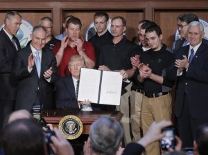 Washington : President Donald Trump, accompanied by coal miners and, from left, Interior Secretary Ryan Zinke, Environmental Protection Agency (EPA) Administrator Scott Pruitt, second from right, Energy Secretary Rick Perry, and Vice President Mike Pence, far right, holds up the signed Energy Independence Executive Order, Tuesday, March 28, 2017, at EPA headquarters in Washington. AP/PTI(AP3_29_2017_000007B)